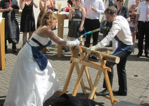 Bride and groom sawing
